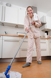 woman in pajamas cleaning the kitchen poster