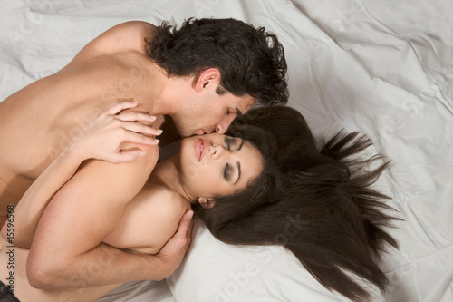 Loving affectionate nude heterosexual couple on bed in affection