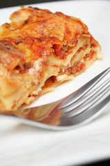 Serving of lasagna on white plate with fork