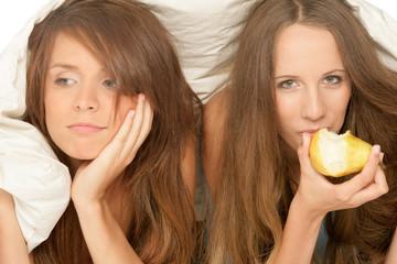 Two teenage girls lying down below duvet