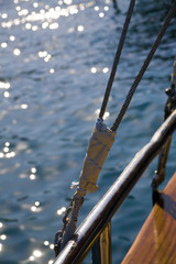 rigging of sail ship and sea waves with the sun specks