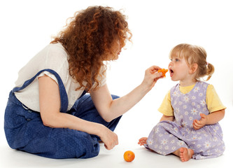 feeding little girl fruit young woman