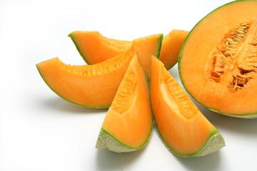 Melon en tranches et un demi-melon sur fond blanc