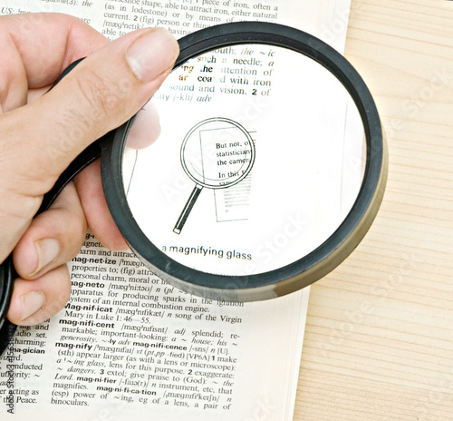 Attentive reader reading dictionary with magnifier glass
