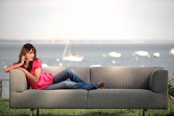 Femme assise sur un canapé téléphonant avec téléphone portable