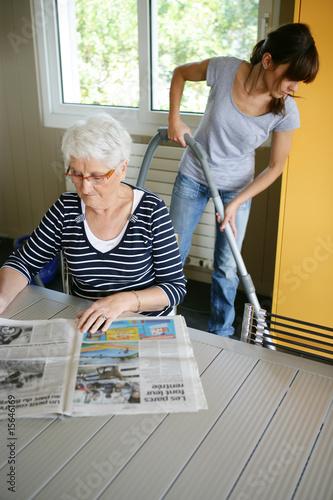 femme s nior assise lisant le journal pr s d 39 une femme de m nage de auremar photo libre de. Black Bedroom Furniture Sets. Home Design Ideas