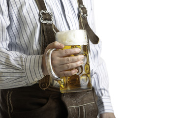 Man with leather trousers holds beer stein at Oktoberfest