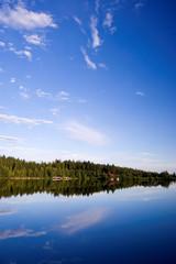 Nadelwald spiegelt sich in See an herrlichem Sommertag