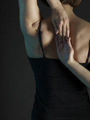 Rear view of woman in yoga position. Hands clasped.