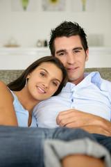 Jeune couple souriants assis sur un canapé