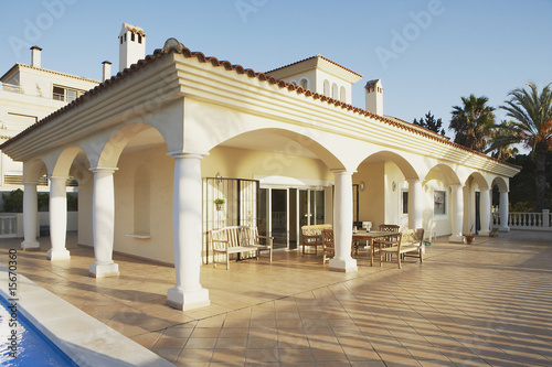 Building with columns and patio furniture on pool deck