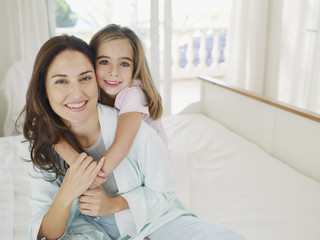 Woman and girl embracing in bedroom smiling