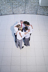 Aerial view of six office workers huddling together