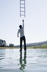 Man standing on water reaching for ladder rear view