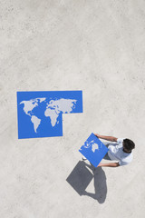 Aerial View of man with piece of world map puzzle outdoors