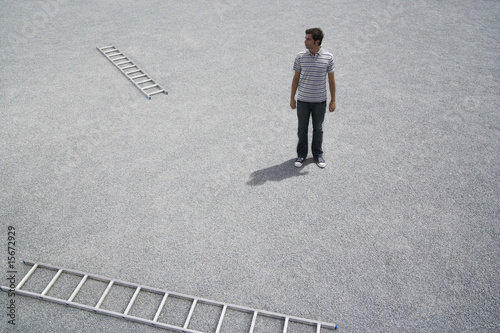Man standing outdoors with two ladders on ground