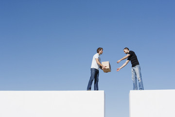 Two men atop two walls passing a box