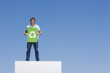 A man holding a recycling sign atop a wall