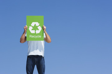 A man holding a recycling sign in front of his face