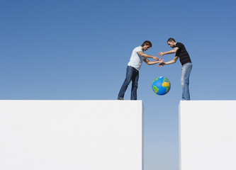 Two men atop a wall dropping a globe