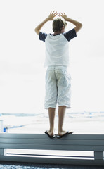 A boy looking out a window at an airport
