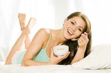 Attraktive Frau frühstückt im Bett