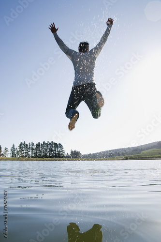 A man jumping overtop of water