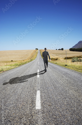 A businessman in the middle of the road walking away