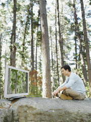 A man watching television outdoors in the woods