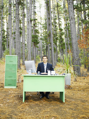 A businessman at his desk in the woods