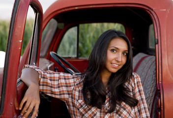 A beautiful woman with her old red pickup truck