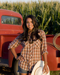 A young woman on a rural farm with an old red truck