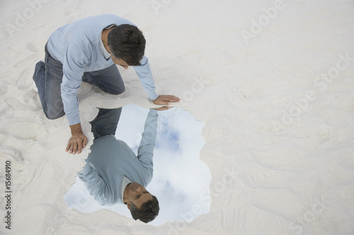 A man looking at his reflection outdoors