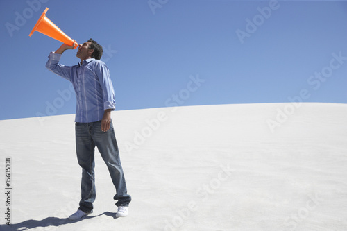 A man with a traffic cone in the middle of nowhere