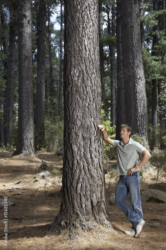 A man leaning on a tree
