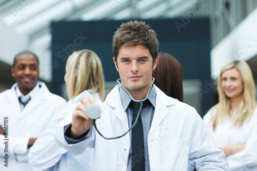 Handsome young doctor in front of his team