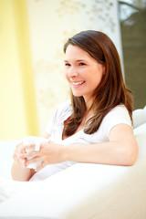 Junge Frau Zuhause mit Kaffeetasse lachend