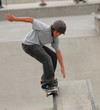 teenage skateboarder doing 50 50 grind on a rail