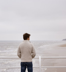 A man on the boardwalk at the beach
