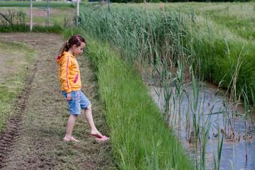 bimba ai margini di un canale di irrigazione