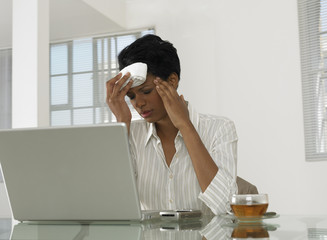 A businesswoman on a laptop with a headache