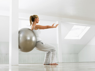 A woman working out with a pilates ball