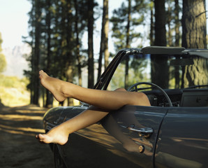 A woman lying in a car relaxing in the woods