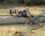 A cyclist taking a break on a log