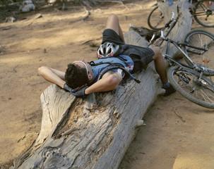 A cyclist taking a break on a log