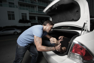 Man stuffing a dead body in the trunk