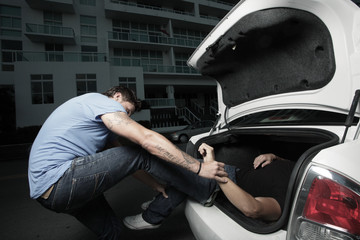 Man stuffing a body in the trunk