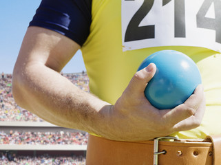 Athlete holding shot-put ball in an arena
