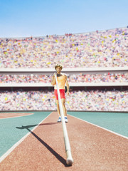 Athlete standing with a pole vault in an arena