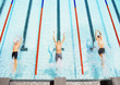 Three swimmers jumping back into a pool